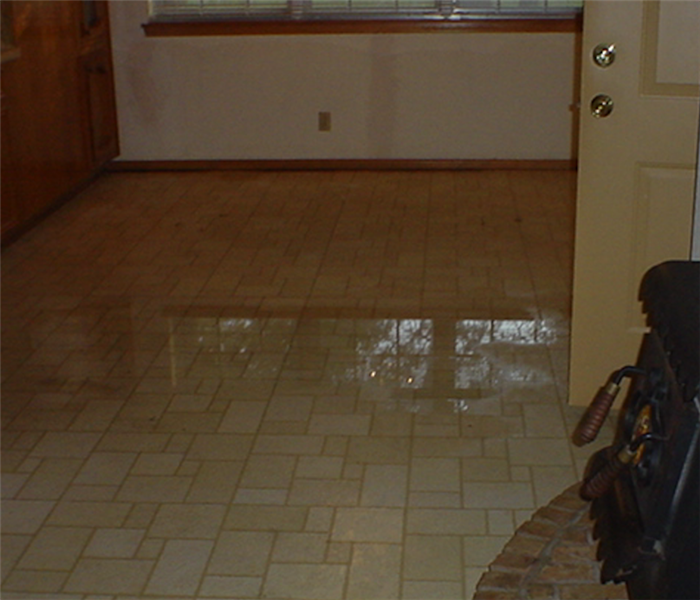 Kitchen area with pool of water in tile floor after a water loss.