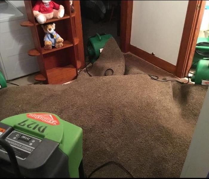 Our green drying equipment set up and running under a carpet in a bedroom that had suffered from water damage.